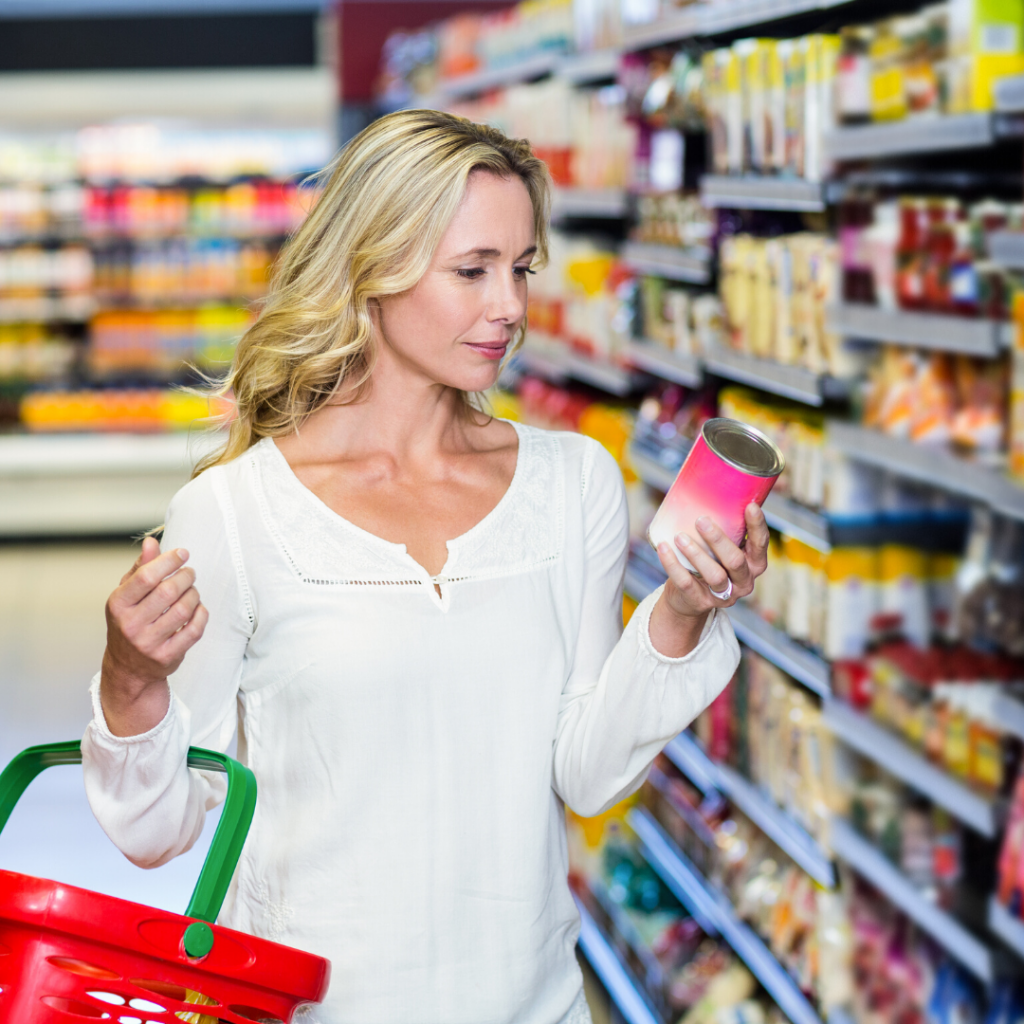 Woman practicing clean eating for beginners, looking at ingredient label on a can in the grocery aisle.